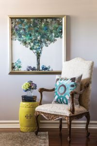 This chair is actually part of a dining set. Malcolm added this Traci Zeller pillow to bring fun and color to an otherwise classic but traditional chair. With the addition of this decorative drum, flowers and a painting, she created a lovely nook.