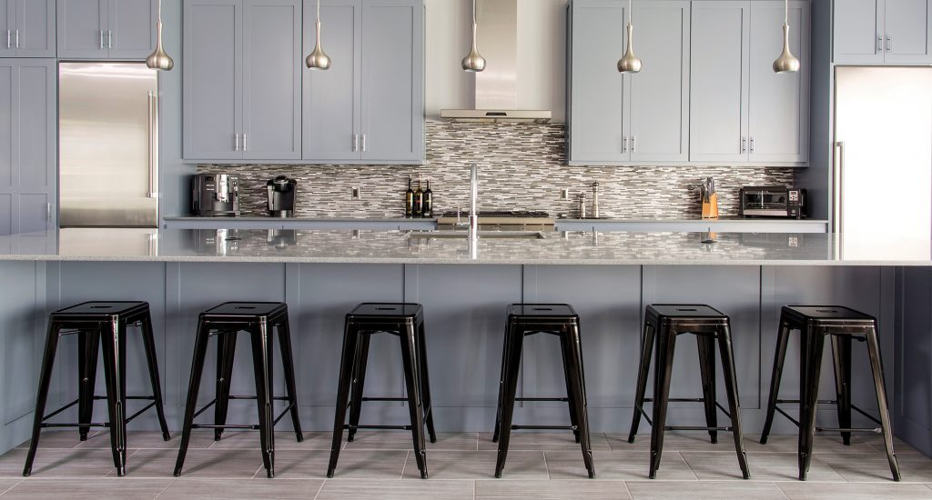 Behind the custom cabinetry, the backsplash of horizontally oriented glass tile by Eleganza Tiles pulls together several of the cool, industrial colors in the room, and adds a layer of texture to the space.