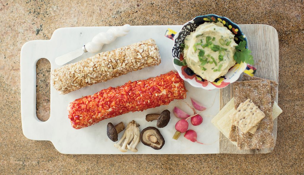 The vegan cheese plate includes cashew cream cheese, almond cheese wrapped in pecans, almond cheese wrapped in fresh red peppers, smoked shitake and oyster mushrooms, and pickled radishes with gluten-free cracklebred, whole grain crispbread and artisan nut-thins with flax seeds.