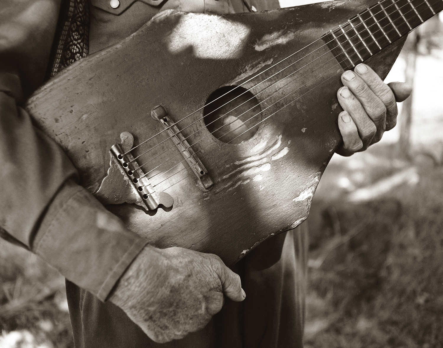 """Ozark folksinger, Jimmy Driftwood, holds his 130 year old hand-made guitar passed down to him by his father. The late Jimmy Driftwood was at one time a high school teacher in the hills of Arkansas and wrote ballads to teach his students their lessons in history. His most famous song was """"The Ballad of New Orleans."""