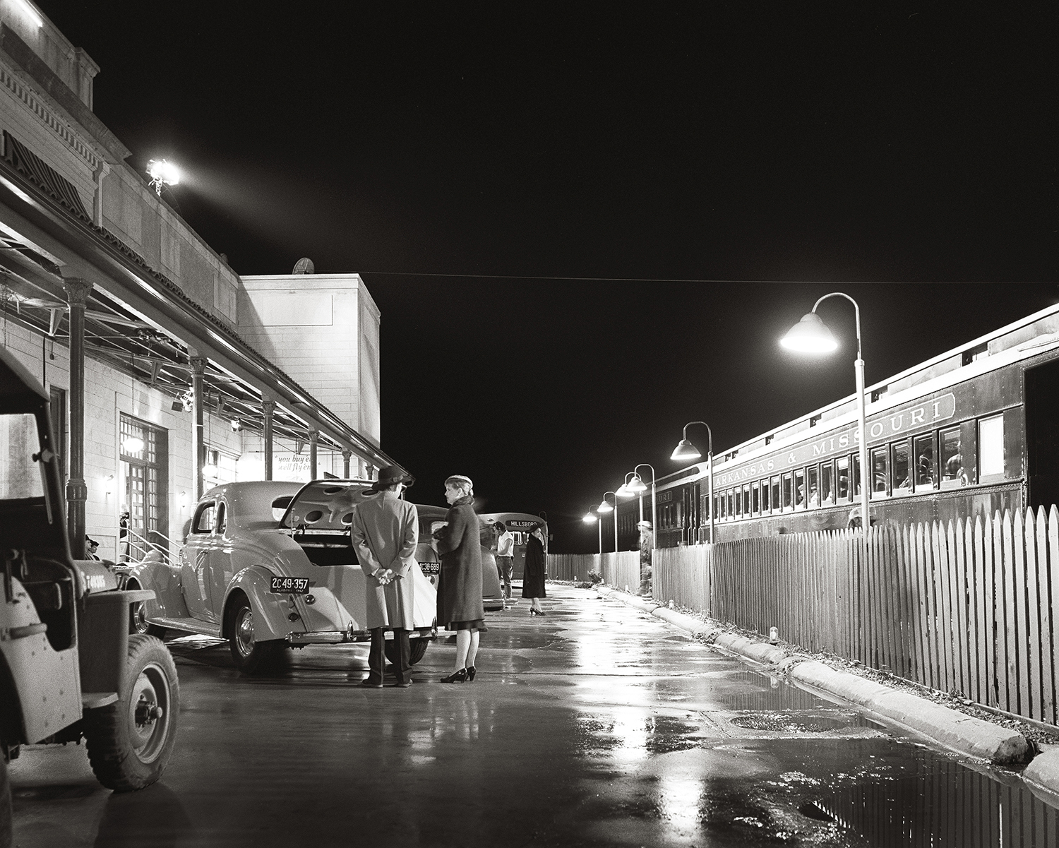 HBO pictures is filming railroad depot scenes at Fort Smith, Arkansas' Frisco Station in 1995. The pavement has been watered to increase specular highlights as actors in vintage clothing use a train operated by the Arkansas and Missouri Railroad