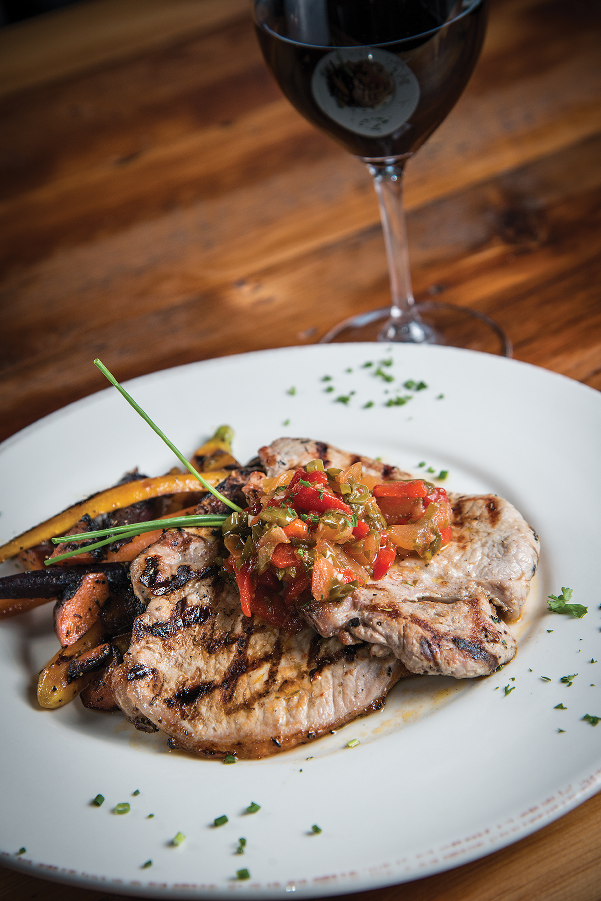 Pork chops, on the grill menu, topped with a tomato garlic reduction and accompanied by roasted vegetables