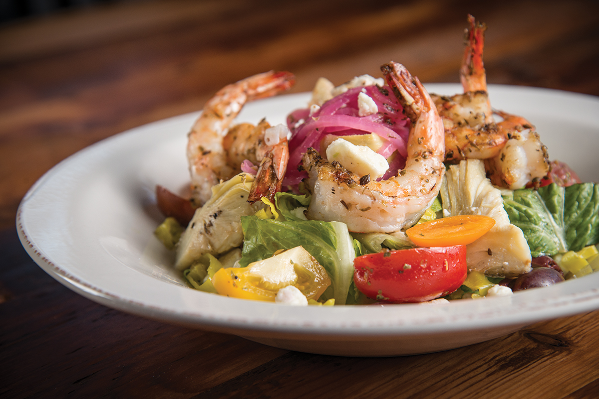 Greek salad topped with grilled shrimp