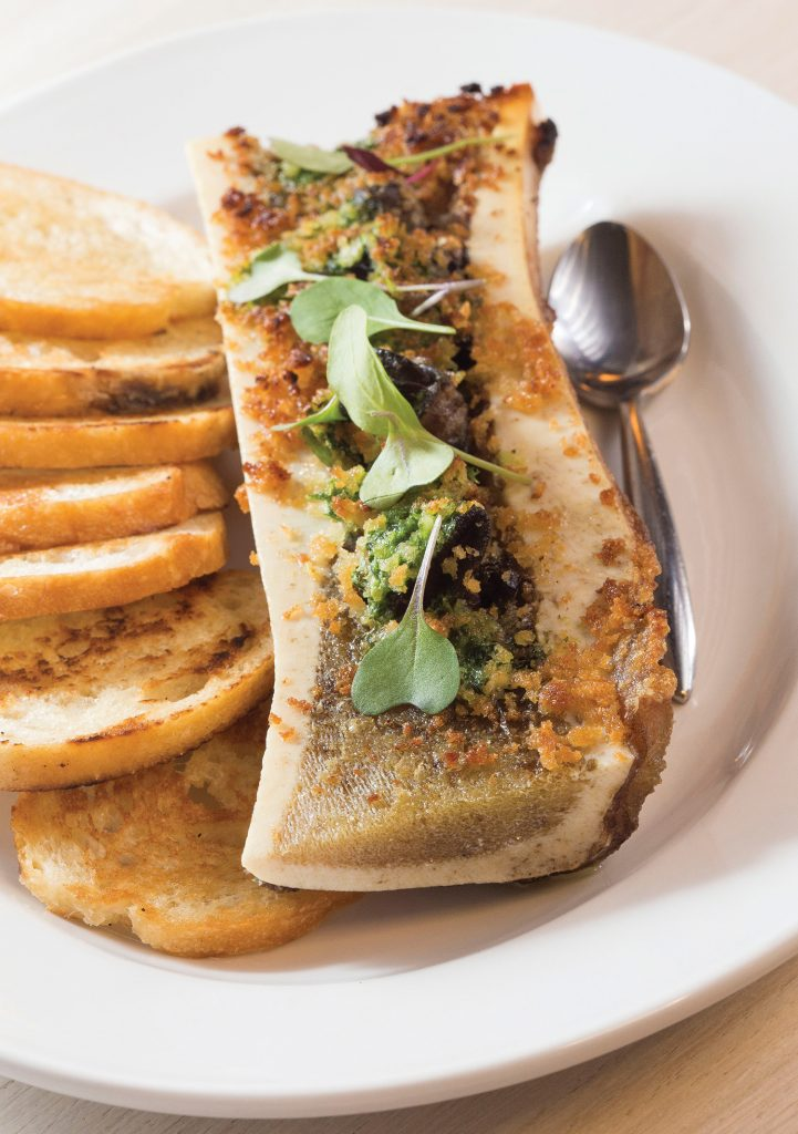 """Table 28's luxurious bone marrow, which is served with escargot, Pernod and lemon. (Top of page) Rains' pork shank """"redemption"""" is just one of the restaurant's beautifully presented entrees."""
