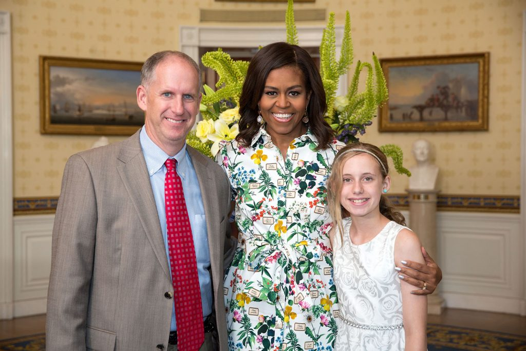 Aspen Smith, 12, with dad Lee and First Lady Michelle Obama at the White House, 2015. Aspen is a guest judge for the 2016 Cupcakes for Goodness Sake. She represented Arkansas at the Kids State Dinner as winner of the Arkansas Lunchtime Challenge. She attends Episcopal Collegiate School in Little Rock.
