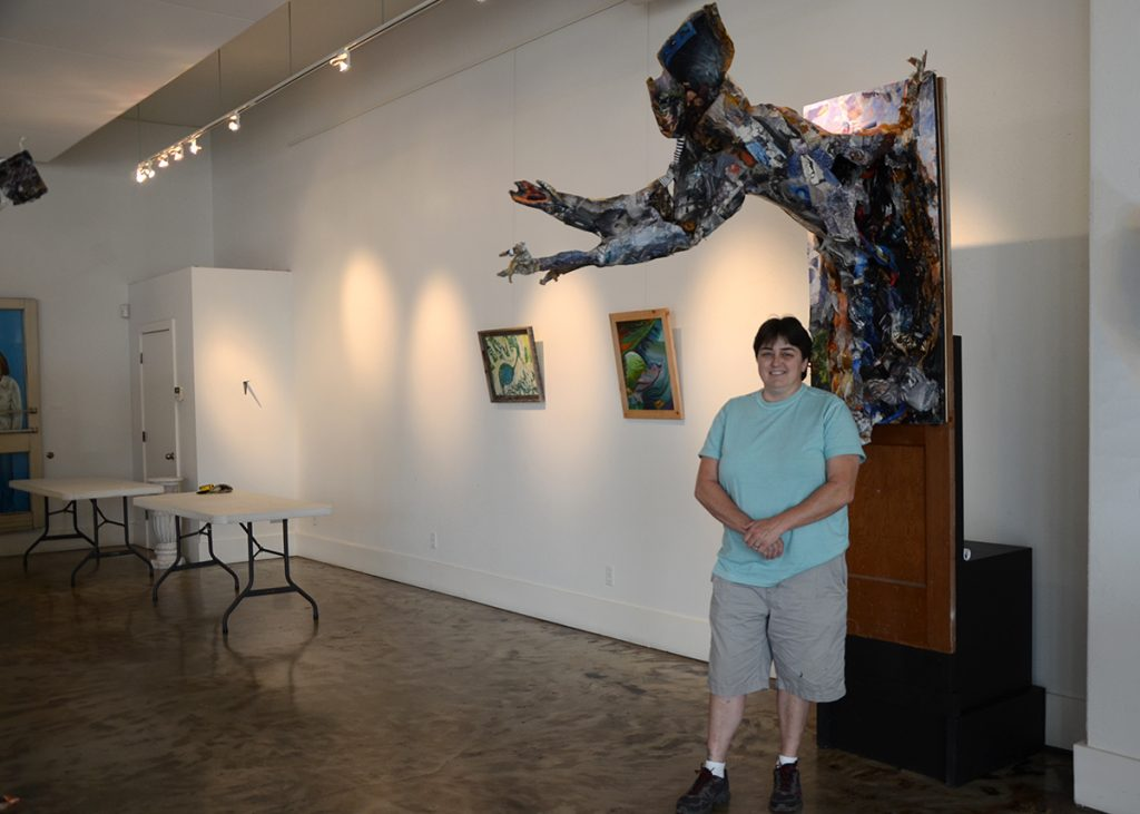 "Artist Sandra Sell in the Thea Foundation gallery, standing amidst her exhibit – ""Curiosity Revealed."" (photos by Becca Bona)"